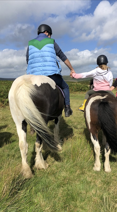 Holding hands whilst horse riding in countryside